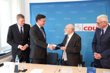 Rolf Zick übergibt CDU-Landeschef David McAllister die Chronik