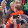 Im Bild ist Dr. Bernd Althusmann zu sehen, wie er einem Helfer die Hand ausstreckt. Der Helfer ist nicht im Bild. Althusmann wird leicht verdeckt von einem Mann, der eine Jacke des Deutschen Roten Kreuzes trägt und mit dem Rücken zur Kamera steht. Um die beiden Männer herum stehen weitere Funktionsträger, Helfer und Journalisten.