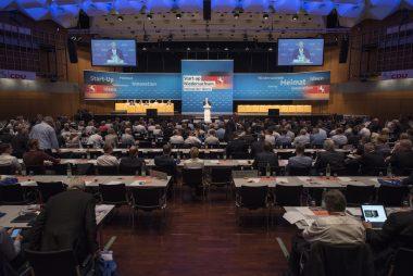 Auf dem Bild ist die Parteitagshalle zu sehen. Der CDU-Landesvorsitzende Dr. Bernd Althusmann spricht der Kamera zugewandt zu den ebenfalls zu sehenden Delegierten. Diese sitzen und haben der Kamera den Rücken zugewandt.