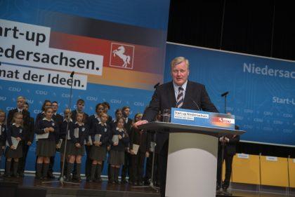 Im Bild ist der CDU-Landesvorsitzende Dr. Bernd Althusmann stehend am Rednerpult zu sehen. Er lehnt auf dem Pult, im Hintergrund stehen einige Kinder des Helmstedter Knabenchors.