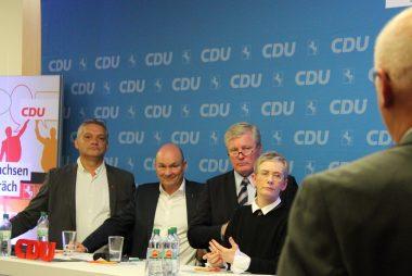 Vorne rechts ist ein stehender Mann von hinten zu sehen. Von links nach rechts blicken Kai Schwabe, Dr. Volker Müller, Dr. Bernd Althusmann und Dr. Petra Bahr in seine Richtung.