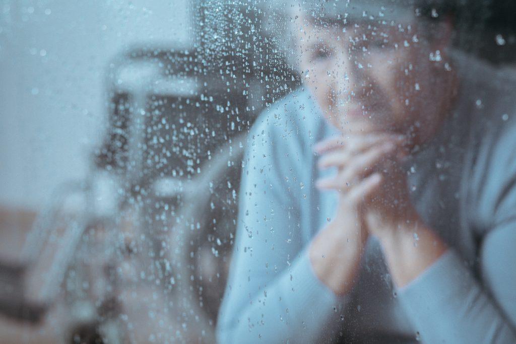 Ältere Frau schaut traurig aus Fenster mit Regentropfen. (Foto: Adobe Stock)